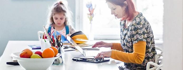 Mutter arbeitet am Laptop während ihre Tochter nebenbei lernt