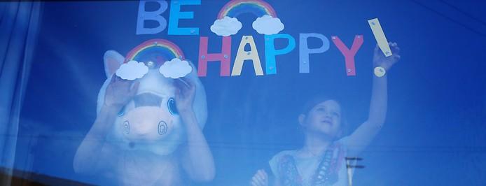 """Mädchen klebt ein Rufzeichen ans Fenster um den Spruch """"Be Happy"""" zu komplettieren, daneben ein Bub mit Pferdemaske"""