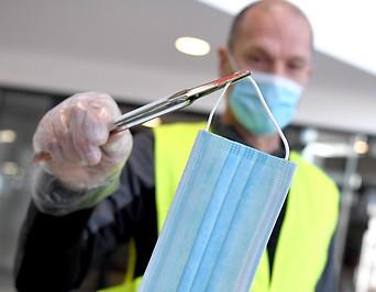 Mitarbeiter verteilt Schutzmasken