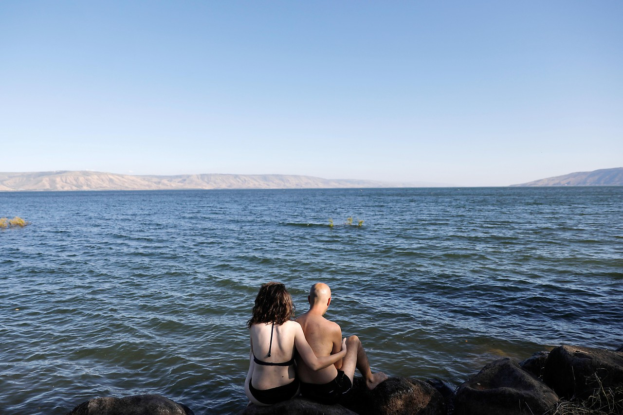 Ein Paar sitzt am Ufer des See Genzareth