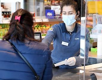 Eine Mitarbeiterin mit Mund- und Nasenschutz in einem Supermarkt
