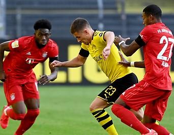 Münchens David Alaba und Alphonso Davies () gegen Dortmunds Thorgan Hazard