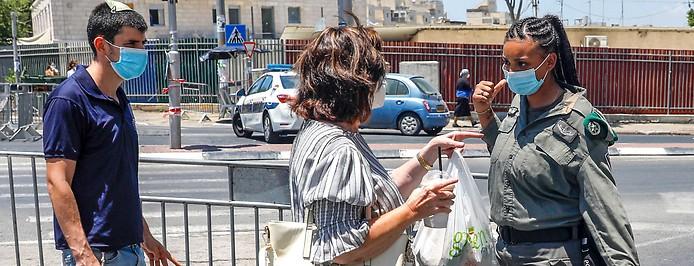 Eine Polizistin hindert eine Frau am Betreten eines Viertels in Jerusalem