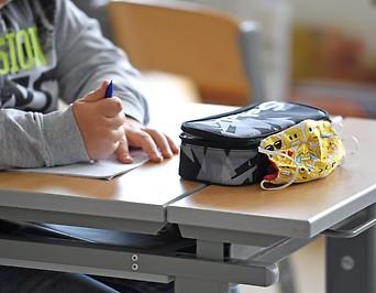 Schutzmaske eines Schülers neben einem Federpennal auf einem Schultisch
