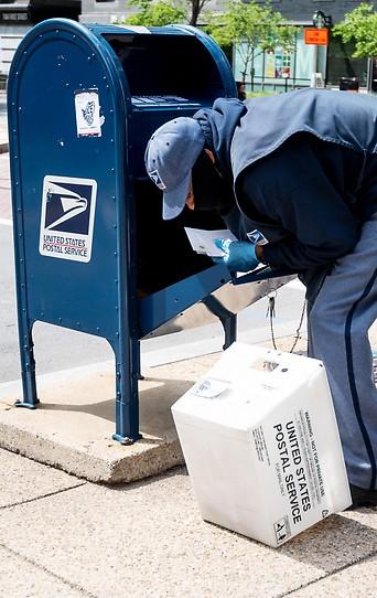 Ein Mann entleert eine Briefkasten der USPS
