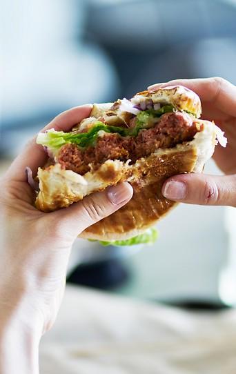 Person isst einen Veggie-Burger