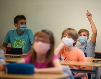 Schüler und Schülerinnen (ca. 12 Jahre) mit Masken in einer Klasse
