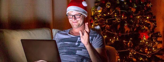 Mann mit Weihnachtsmütze vor einem Laptop