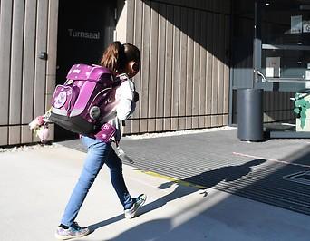 Schulkind vor dem Eingang einer Schule