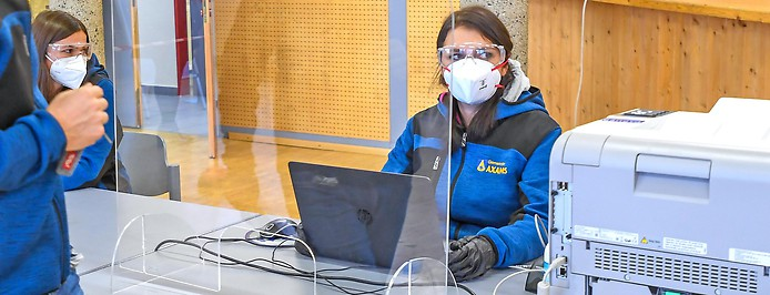 Eine Frau mit Schutzmaske und -brille sitzt an einer Coronavirus-Teststation vor einem Laptop