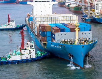 Containerschiff bei der Beladung im Hafen von Qingdao, China