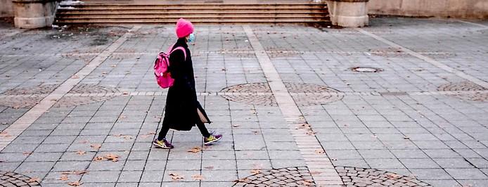 Eine Frau mit Schutzmaske auf einem Platz in Frankfurt