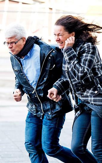 Eine Frau und ein Mann bei starkem Wind auf der Straße