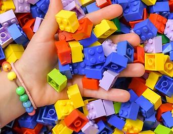 Hand greift in große Menge an LEGO Steinen