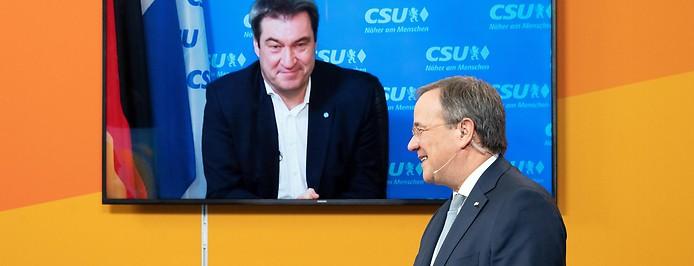 Der bayerische Ministerpräsident und CSU-Chef Markus Söder auf einem Bildschirm und im Vordergrund NRW-Ministerpräsident und CDU-Chef Armin Laschet