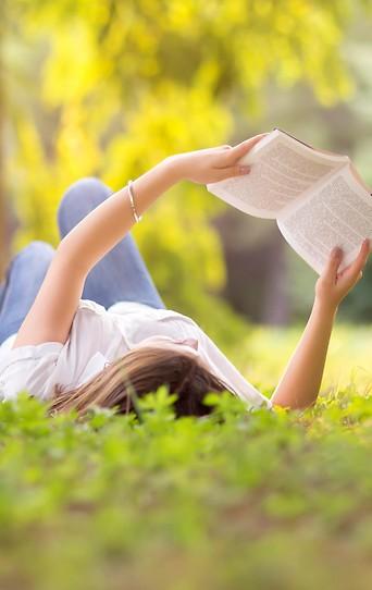 Frau beim Lesen in einer Wiese