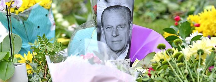 Ein Schwarz-Weiß-Foto von Prinz Philip umgeben von Blumensträußen