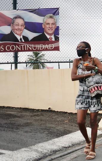 Eine Frau geht in Kuba an einem Plakat mit Raul Castro, Fidel Castro und Kubas Präsidenten Miguel Díaz-Canel vorbei