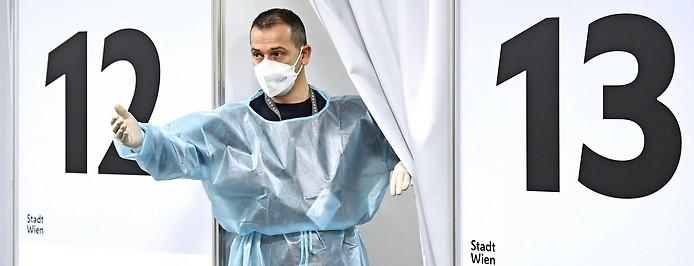 Ein Mann mit Schutzkleidung bittet eine Person in eine Impfstation