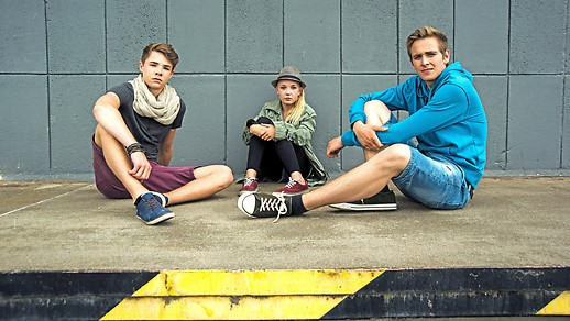 Ein Mädchen und zwei Burschen sitzen auf einem Gehsteig