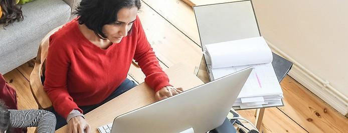 Eine Frau arbeitet im Wohnzimmer im Home Office