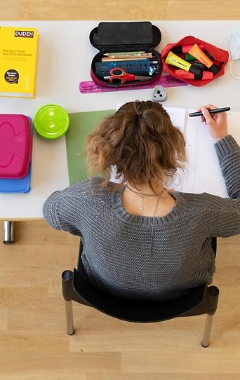 Eine Schülerin mit Federpenal, Stiften und Duden