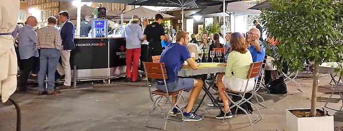 Gäste sitzen nachts im Gastgarten eines Lokals in der Salzburger Innenstadt