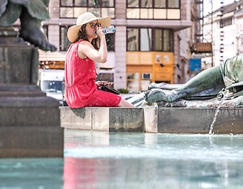 Eine Frau sitzt am Rand eines Springbrunnens und trinkt aus einer Wasserflasche