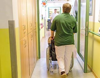 Eine Pflegerin schiebt auf einem Gang einen Heimbewohner im Rollstuhl