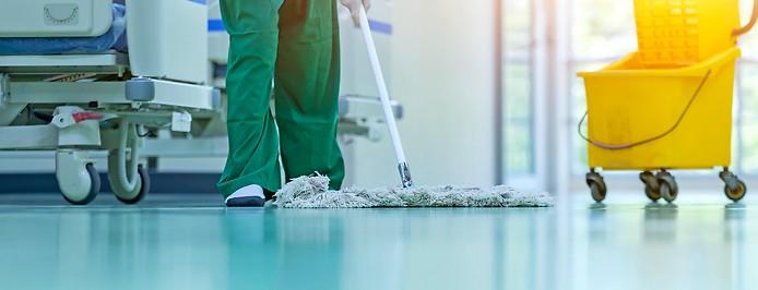 Eine Reinigungskraft putzt den Boden in einem Krankenhauszimmer