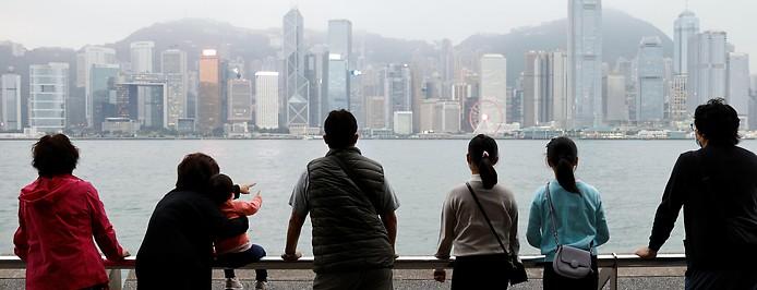 Menschen schauen von Aussichtsplattform auf die Skyline von Hongkong