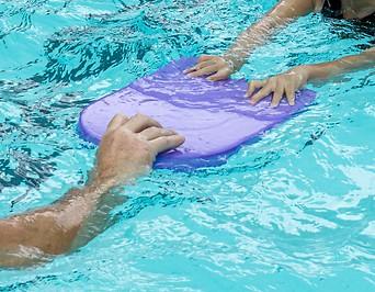 Ein Kind hält sich an einer Schwimmhilfe fest