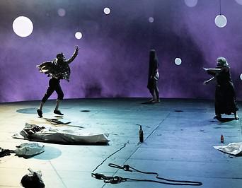 Szenenbild Figuren im Dunkel wilde Kreise auf der Bühne
