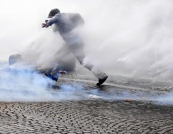 Ein Demonstrant in Paris flieht vor dem Tränengas der Polizei