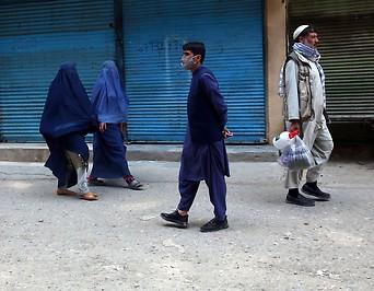 Bewohner in Afghanistan gehen vor geschlossenen Geschäften vorbei