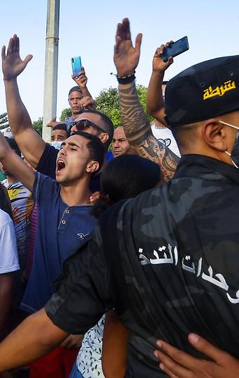 Sicherheitskräfte stehen vor schreienden und gestikulierenden Demonstranten