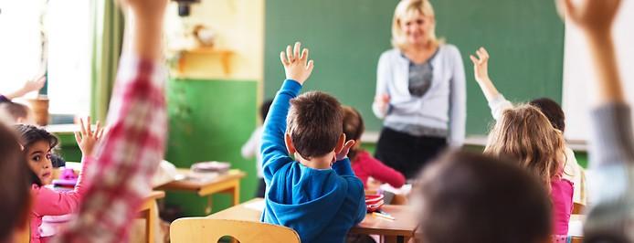 Kinder in einer Schulklasse heben die Hand
