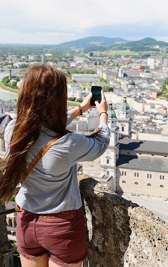 Eine Frau macht ein Foto von der Stadt Salzburg
