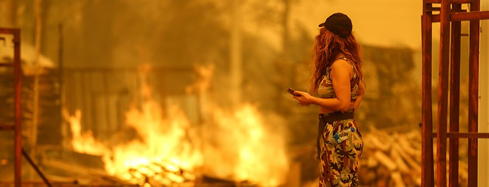 Frau vor verbranntem Haus