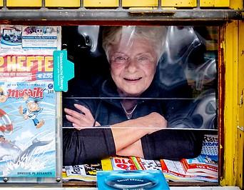 Trafikantin blickt aus ihrem Zeitungskiosk
