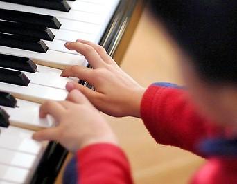 Ein Kind sitzt an einem Klavierflügel
