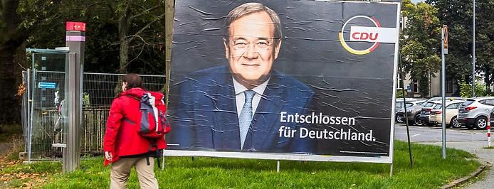 Frau geht an einem Wahlplakat von Armin Laschet (CDU) vorbei
