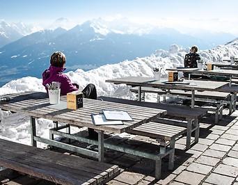 Restauranttische und -bänke im Winter mit Blick auf Berge
