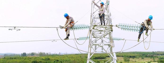 Chinesische Arbeiter auf Hochspannungsleitung