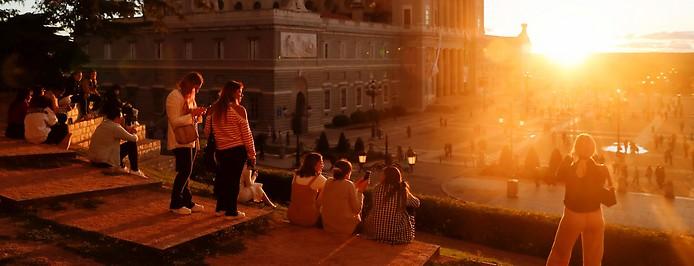 Touristen genießen die herbstliche Abendsonne in Madrid