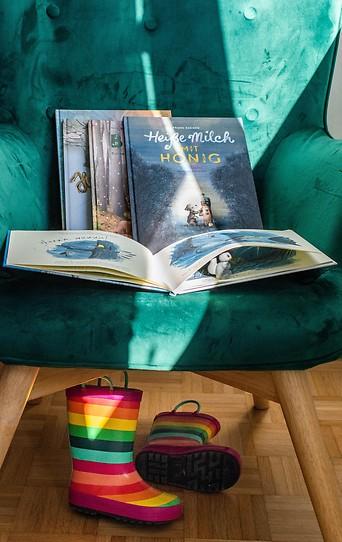 Herbstbücher für Kinder liegen auf einem grünen Ohrensessel