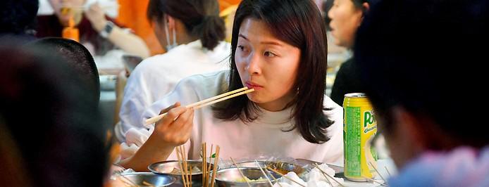 Chinesische Frau isst mit Stäbchen